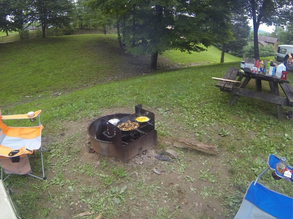 a campfire with two pans cooking food on a grill at a campsite