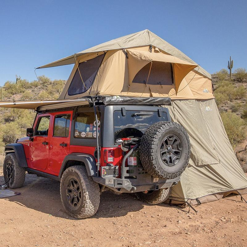 Red jeep with tent on top in desert