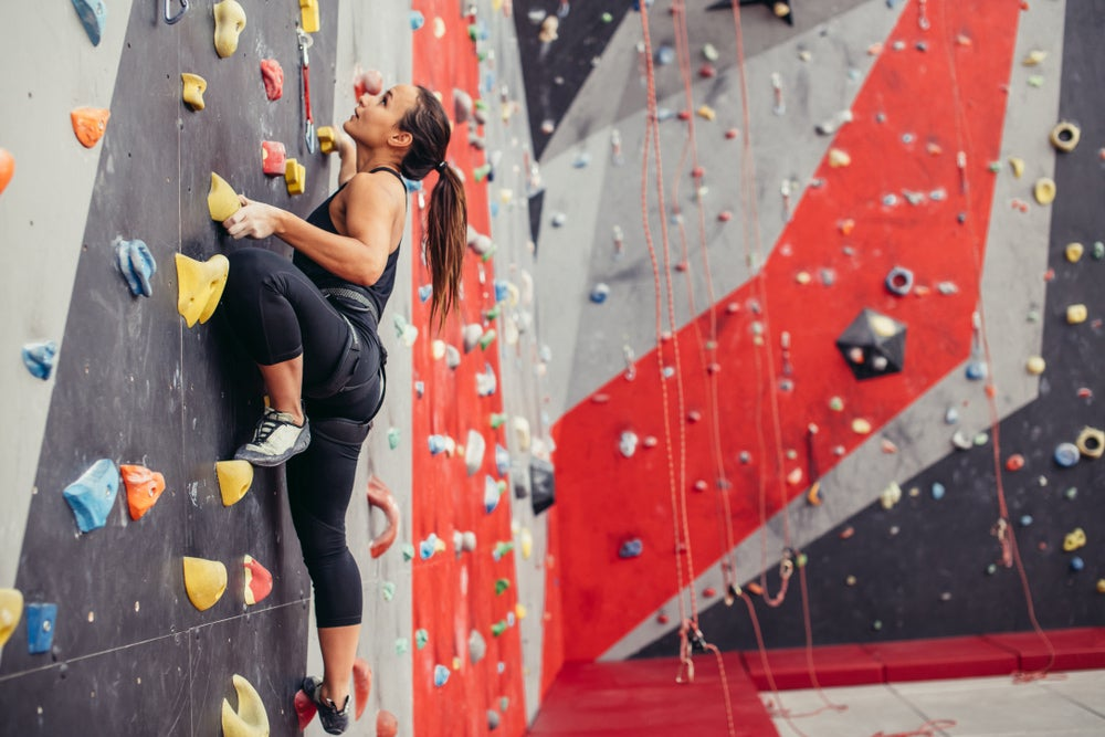 a woman in a glimbing gym going up rocks