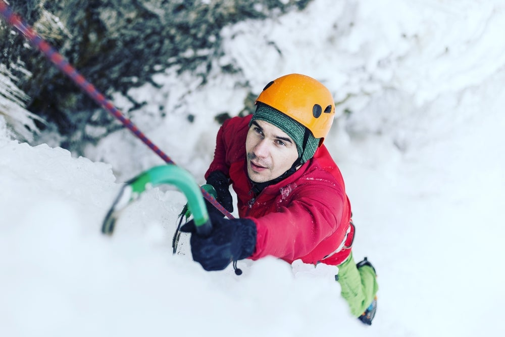 a man climbing close up on ice in alpine conditions