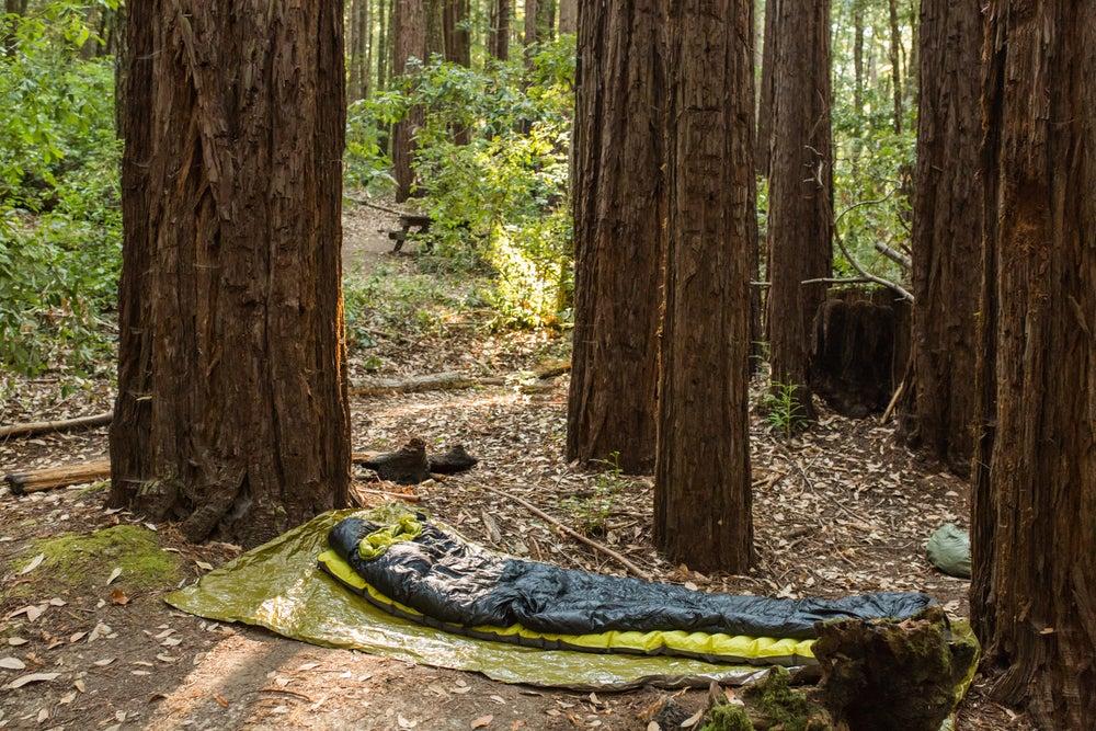 Minimalist campsite of sleeping bag on small tarp.