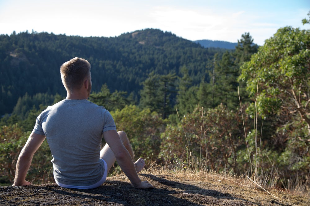 a man sitting on a hill in his underwear outdoors