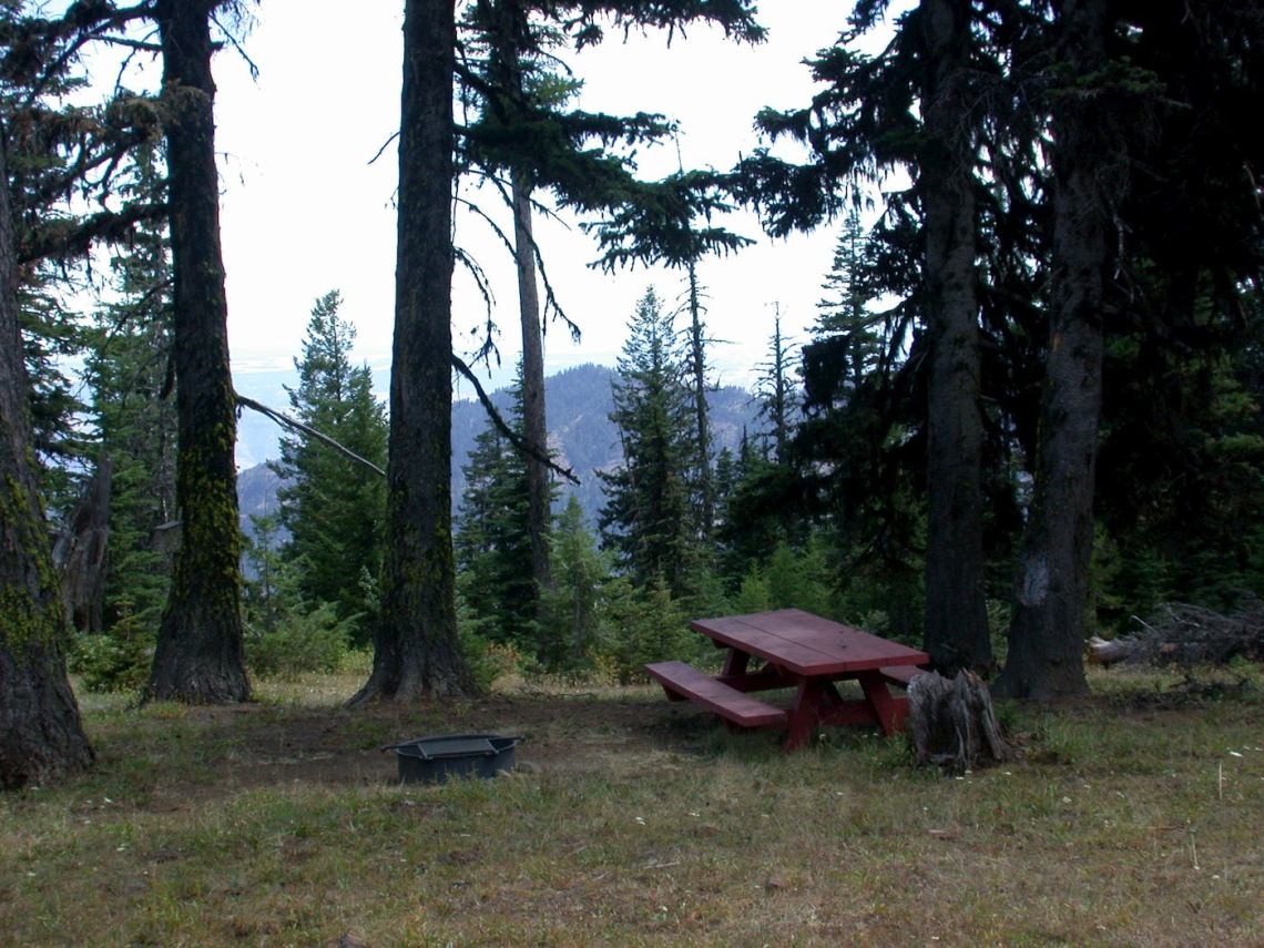 Picnic table and fire pit campsite overlooking hills.