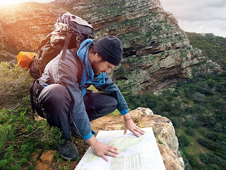 hiker with map in wilderness