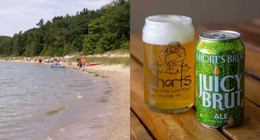 a shoreline on lake michigan next to .a can and glass of beer on a table