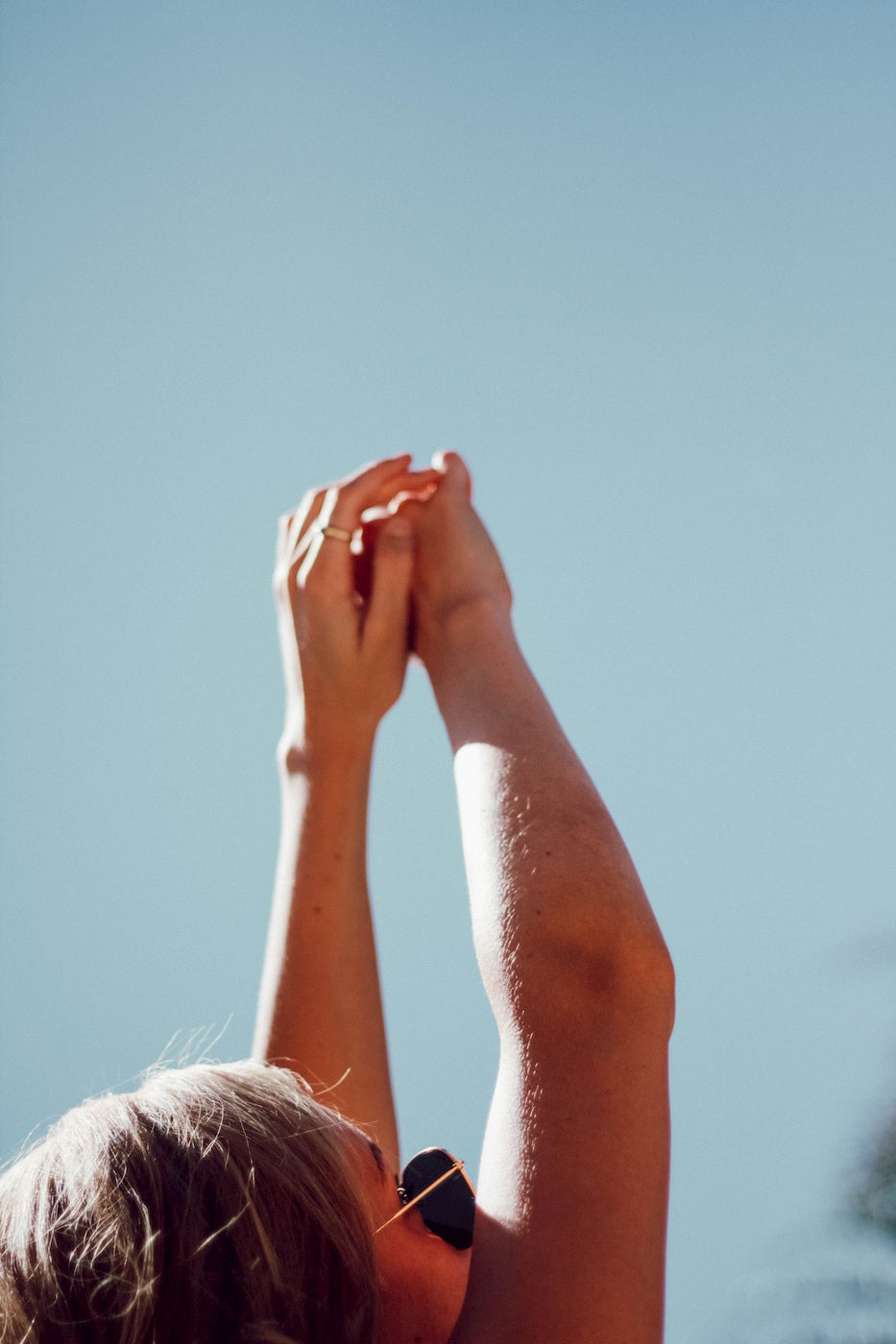 Women stretching her hands up towards the sky on a sunny day.