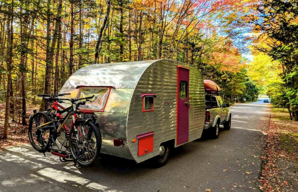 Pickup truck hitched to chrome Trailer with bike rack in Maine autumn foliage.