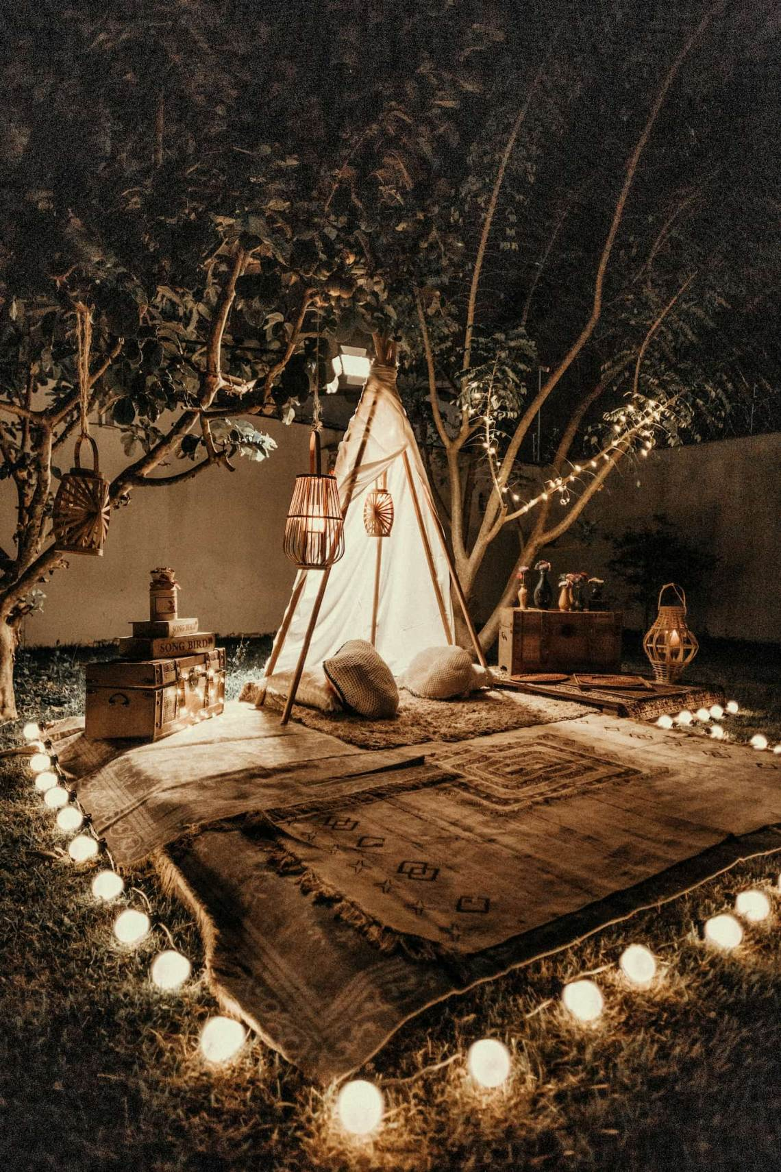 Glamping site setup in a backyard with lanterns and rugs.