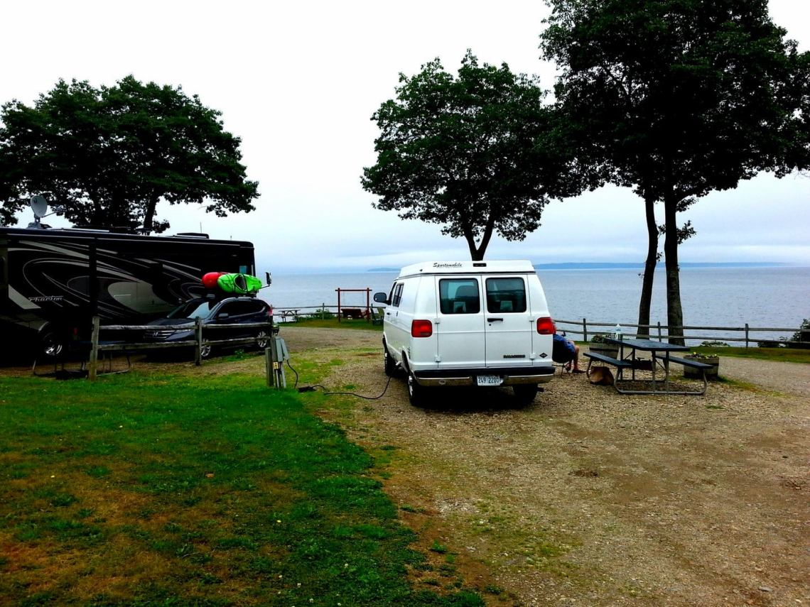 Van parked in campsite beside picnic table, trees, and the ocean.