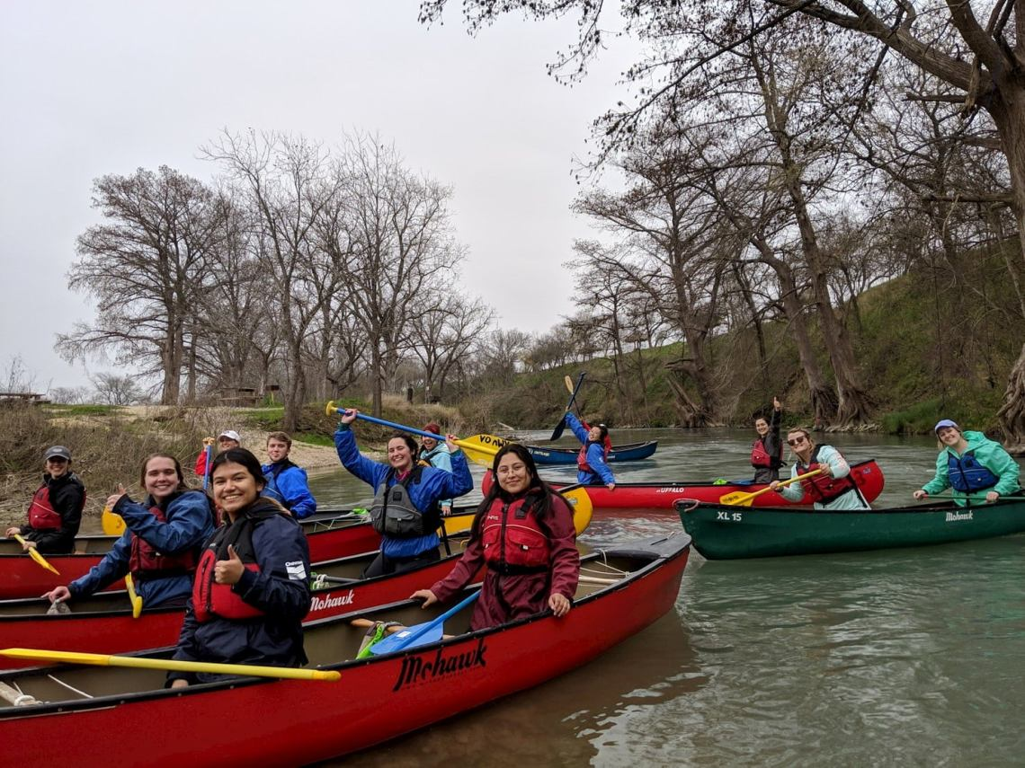 Group of people canoeing on the San Marcos river.