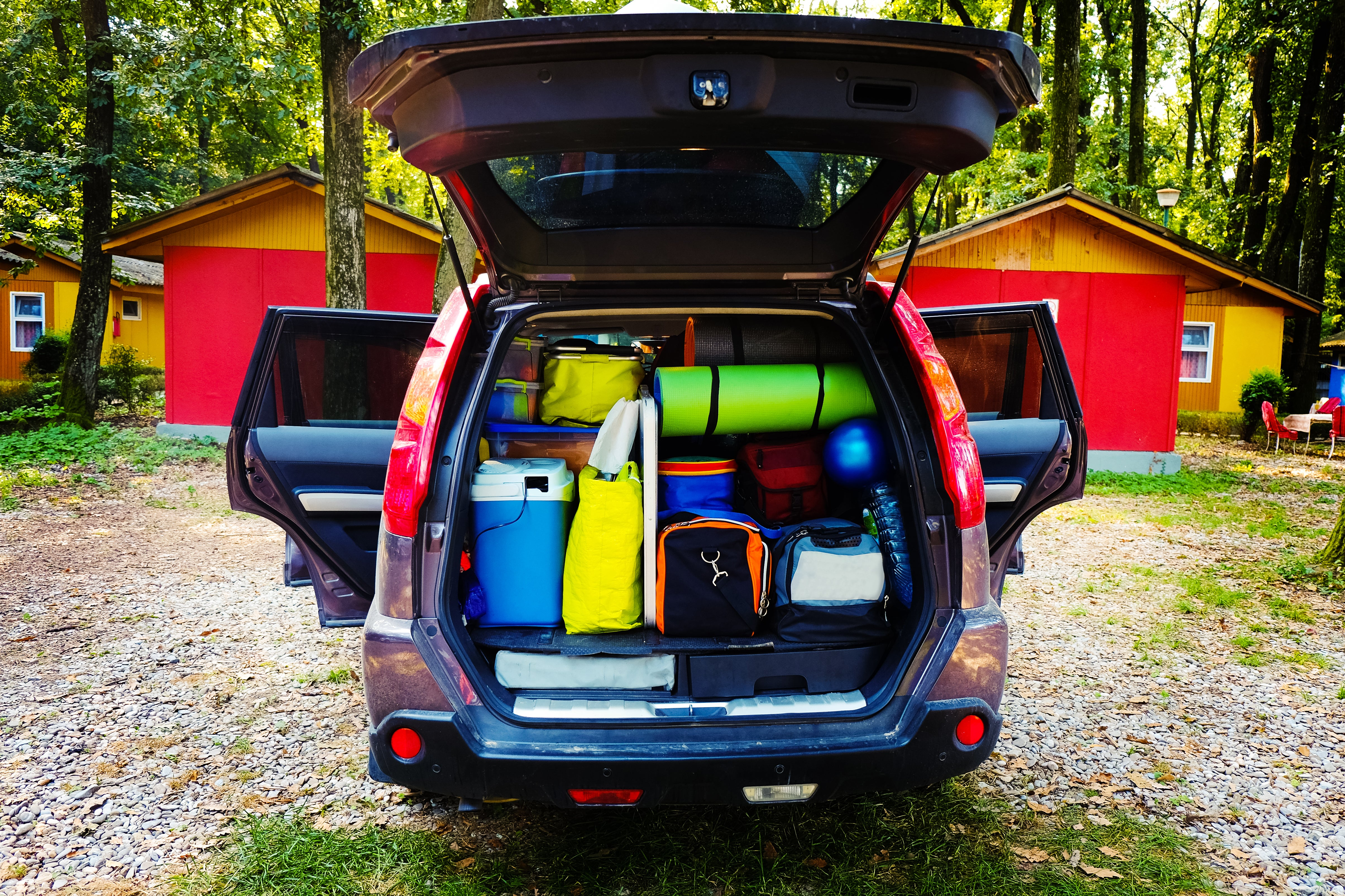 back of car with trunk open, full of camping gear