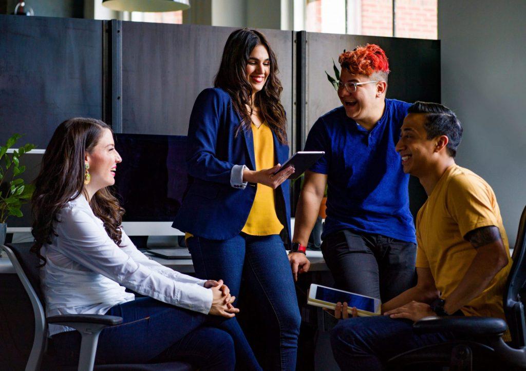 Pessoas na empresa em um momento de descontração realizando uma reunião, ótima para estratégia de uma boa comunicação corporativa