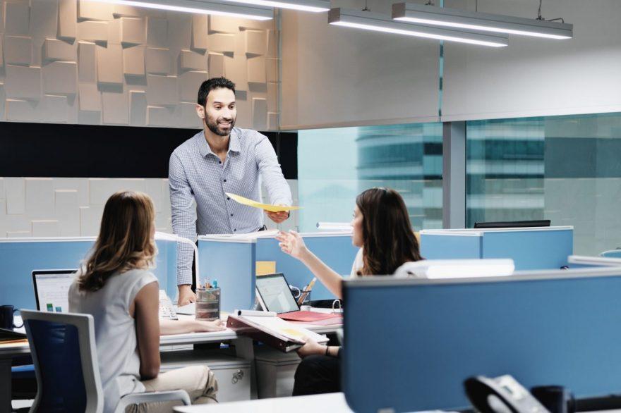 Duas mulheres e um homem no escritório. O homem está entregando um documento à uma das mulheres.