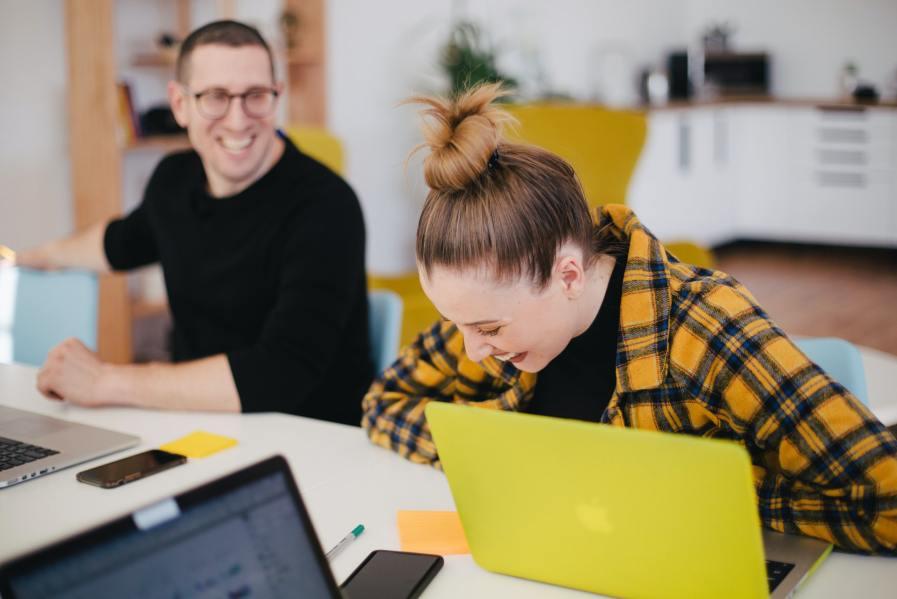 Duas pessoas rindo e conversando enquanto trabalham.