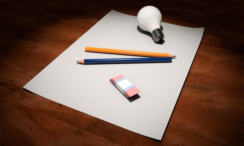 Uma lâmpada, dois lápis e uma borracha por cima de um papel.