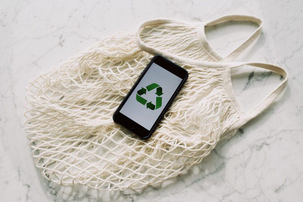 Uma sacola de papel e um celular com o símbolo da reciclagem.