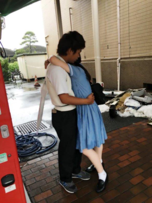 彼氏に抱きつく水色セーラー服を着た清楚系女子高生