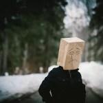 悲しい表情を書いた紙袋を被った男性の写真