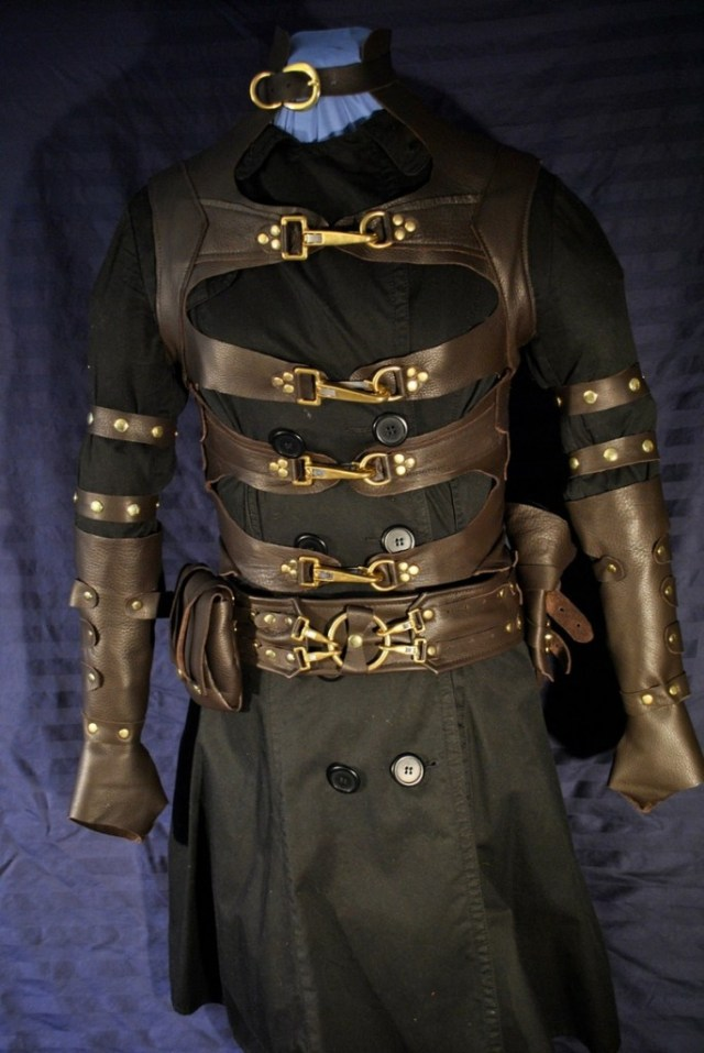 This steampunk-inspired men's leather costume with brass accents features a long, four-strap vest, a belt and bag, a gun holster, and leather gauntlets. Perfect for diceless and BYOB (bring your own backstory). Ragged Edge Leatherworks at CustomMade.com