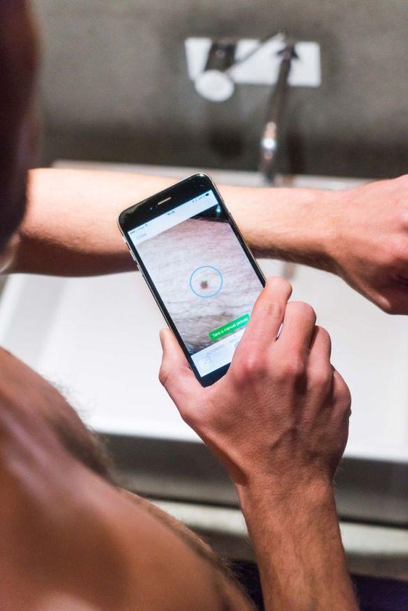 Exemple d'utilisation d'une application du domaine de la e-santé. Ici, un homme utilise son smartphone pour analyser un grain de beauté.