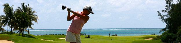 Woman swinging golf club in tropical location