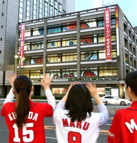 もみじ銀行本店の窓に現れた巨大な「カープ坊や」=11日午後5時42分、広島市中区、上田幸一撮影