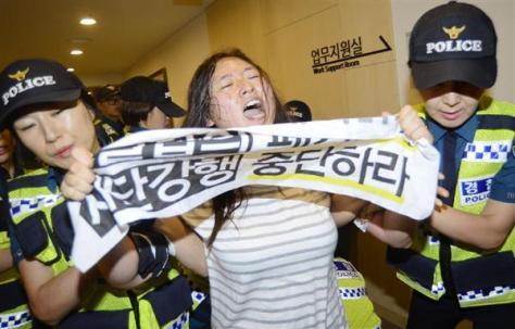 「和解・癒やし財団」の設立に反対し、記者会見場に乱入、警察官に連行される市民団体メンバー=7月28日、ソウル(共同)