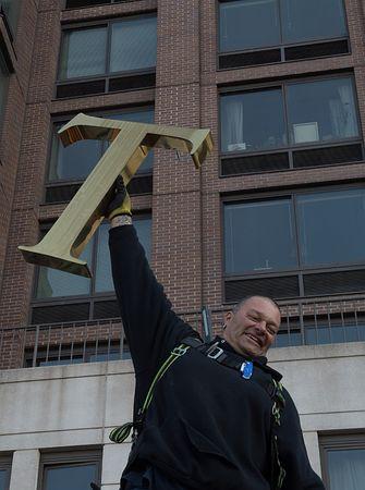 16日、ニューヨーク中心部マンハッタンのビルからドナルド・トランプ氏の名前の文字盤を撤去した作業員(AFP=時事)