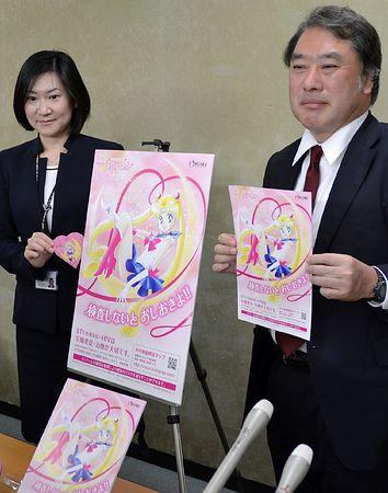 「美少女戦士セーラームーン」のイラストが描かれた性感染症予防啓発のポスターやリーフレットを手に持つ厚生労働省の担当者=21日午後、東京・霞が関