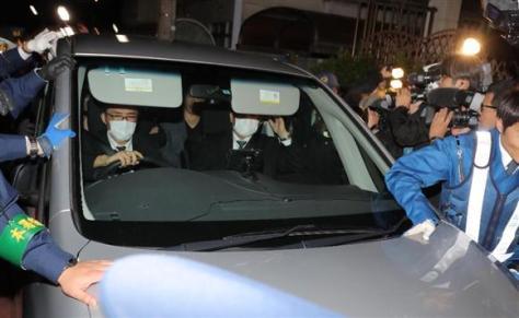 歌手のASKA(本名・宮崎重明)容疑者の乗り込んだ車を警備する警察官と取り囲む報道陣=28日午後、東京都目黒区(早坂洋祐撮影)