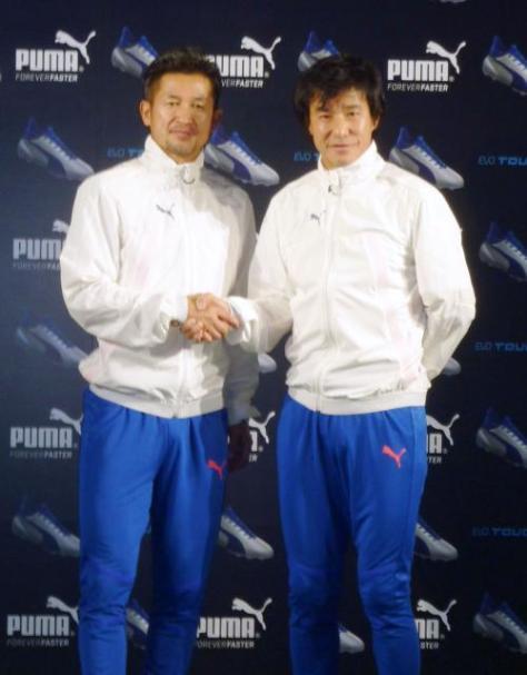 東京都内でのイベントに出席し握手を交わすサッカー元日本代表の三浦知良(左)と中山雅史(共同)