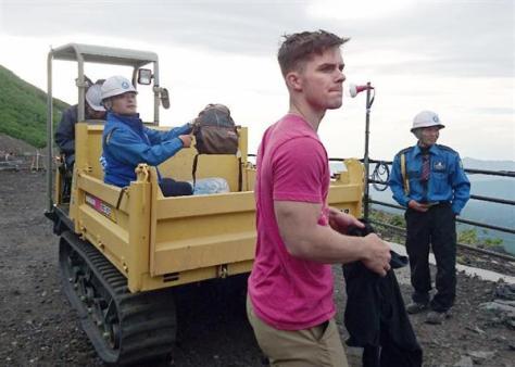 富士山6合目の安全指導センターで運搬車とともに待機するクリストファー・エムスさん(手前)=3日(認定ドローンパイロット山田亘さん提供)