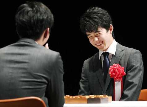 公開対局で都成竜馬四段(手前)に敗れたが、笑顔で対局を振り返る藤井聡太四段