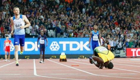 男子400メートルリレー決勝 脚を痛めて倒れ込むジャマイカのアンカー、ボルト(手前右)=ロンドン(共同)