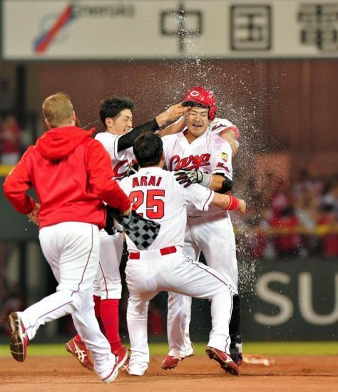 11回、サヨナラ適時打を放ちナインから水をかけられる会沢(中央)=マツダスタジアム