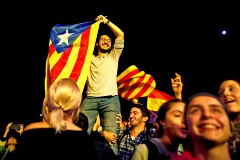 独立住民投票が終わった後、バルセロナの広場でカタルーニャの旗を掲げる男性(1日)=ロイター