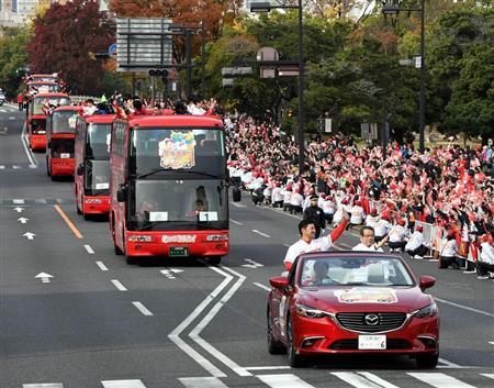 沿道のファンに手を振りながらパレードする広島の選手たち