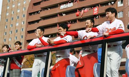 プロ野球広島カープのセ・リーグ連覇を祝うパレードでファンの声援に応える新井選手(右端)ら=広島市