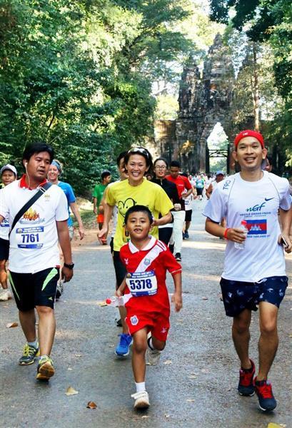 参加ランナーとともに遺跡内を駆け抜ける有森裕子さん(中央奥)=3日、カンボジア北西部シエムレアプ(共同)