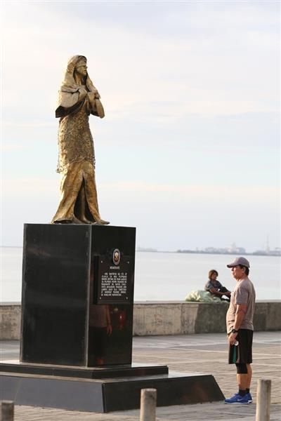 12日、フィリピンのマニラ湾に面した遊歩道に建った慰安婦像を見つめる人