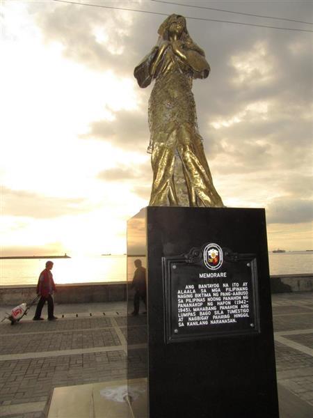 12日、フィリピンのマニラ湾に面した遊歩道に建った慰安婦像が夕日に浮かぶ