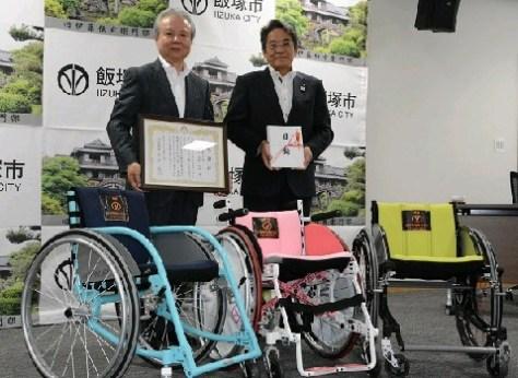 吉塚精機が開発した車いすと高鍋政嗣社長(左)、片峯誠・飯塚市長