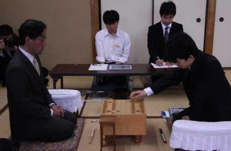 2手目を指す後手の藤井聡太七段。左は深浦康市九段