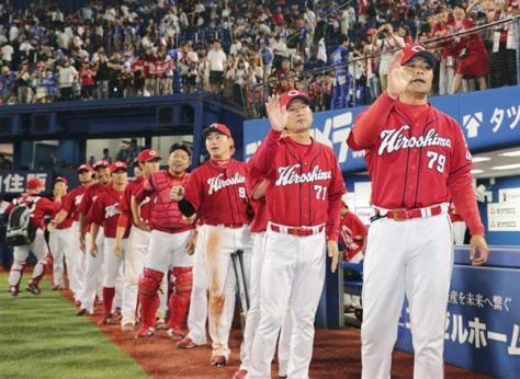 優勝へのマジックナンバーが再点灯し、選手を出迎える広島・緒方監督(右端)=18日、横浜