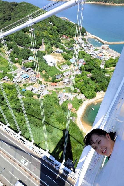 瀬戸大橋の鉄塔の「穴」から顔をのぞかせる福田朱里さん。高さを実感できるツアー体験の一環だ=安冨良弘撮影