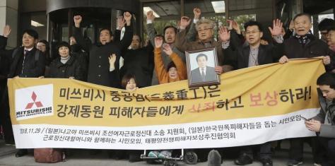 韓国最高裁の判決を受け万歳する原告ら=29日(AP)