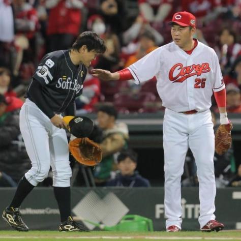 試合前、挨拶するソフトバンク・内川(左)の肩を叩く広島・新井(カメラ・岩下 翔太)