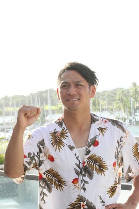 ホテルから見えるハワイの景色を背にポーズを決める田中