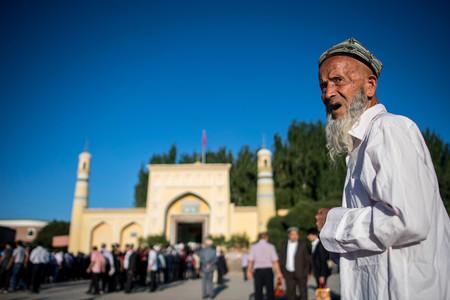 新疆ウイグル自治区でモスク(イスラム礼拝所)前に集まるイスラム教徒の男性(右)=2017年6月、カシュガル(AFP時事)
