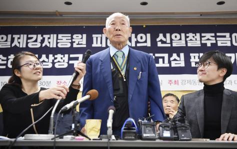 韓国徴用工訴訟で新日鉄住金に賠償を命じた判決が確定し、記者会見する原告の男性(中央)と支援者ら=2018年10月、ソウル(共同)